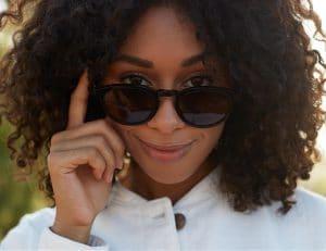 woman peering over her Pala sunglasses